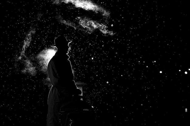 Dramatyczna sylwetka niebezpiecznego mężczyzny w kapeluszu w nocy w deszczu w mieście w starym stylu kryminalnym noir
