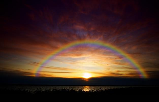 Dramatyczna tęcza uchwycona podczas zachodu słońca w tle krajobrazu