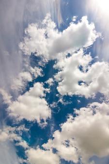 Dramatyczne błękitne niebo z bufiastymi białymi chmurami w jasny jasny słoneczny