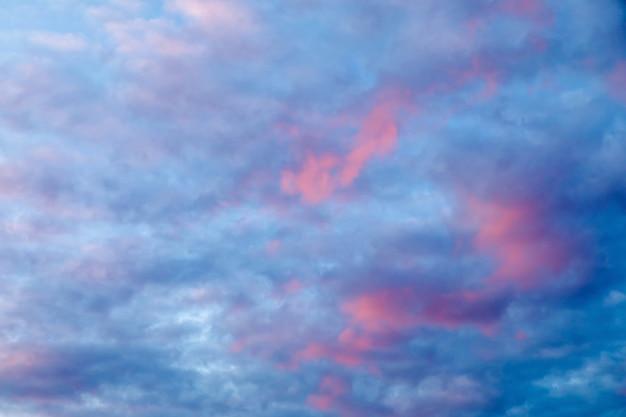 Dramatyczne błękitne niebo z różowymi chmurami o zachodzie słońca.
