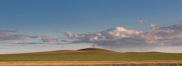 Dramatyczne burzowe chmury nad tundrą oświetloną światłem słonecznym. wzgórze porośnięte zielono-żółtą trawą.