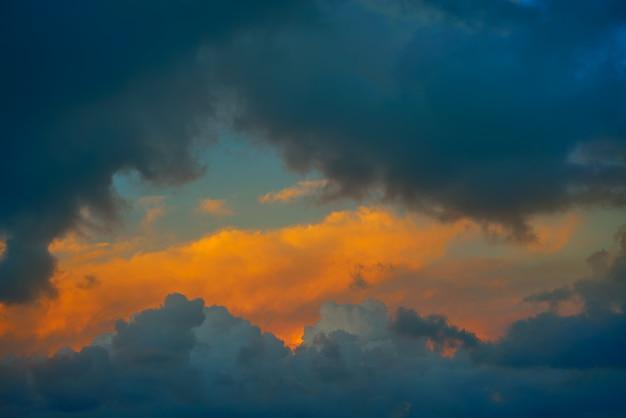 Dramatyczne chmury przy zmierzchu pomarańczowym niebem