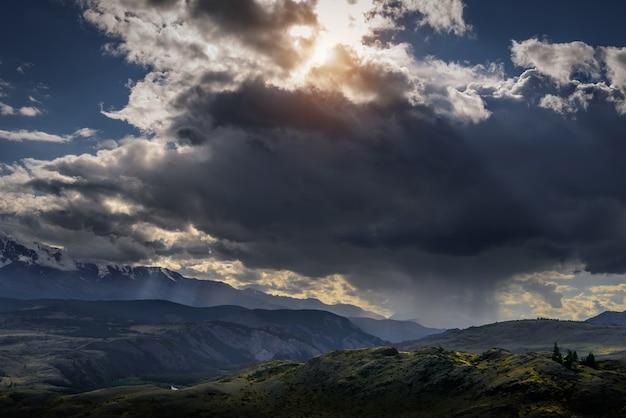 Dramatyczne ciemne chmury w górach przed burzą. krajobraz z pasmem górskim, chmurami deszczowymi i promieniami słońca. epickie tło naturalne.