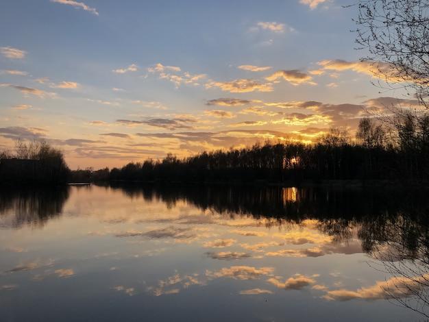 Dramatyczne niebo o zachodzie słońca, chmury odbijają się w nieruchomej tafli wody leśnego jeziora, nagie drzewa zarysowane na horyzoncie
