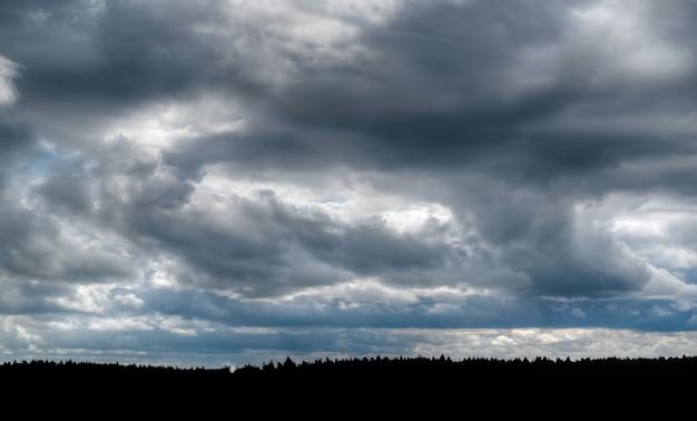Dramatyczne niebo z ciemnymi, skumulowanymi chmurami, może służyć jako tło.