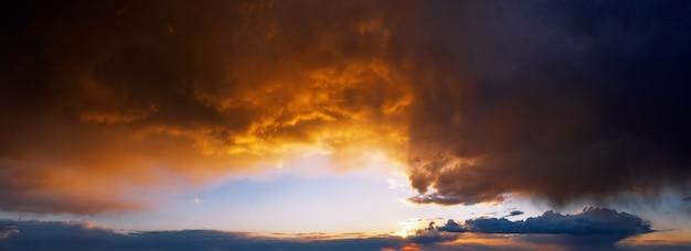 Dramatyczne niebo zachód słońca z ciemnymi deszczowymi chmurami oświetlone słońcem.