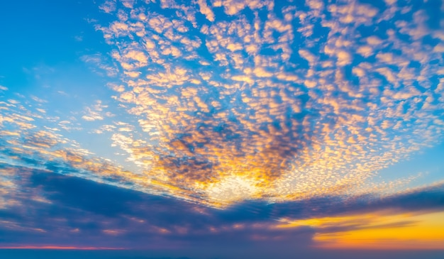 Dramatyczne niebo zachód słońca z pomarańczowymi chmurami i słońcem.