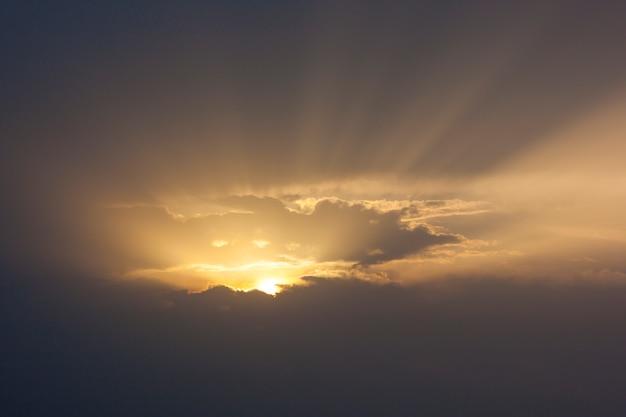 Dramatyczne niebo zachód słońca z wiązki światła przez chmury