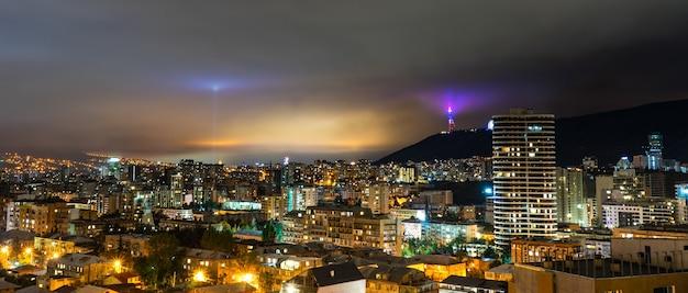 Dramatyczne nocne niebo ze światłem księżyca przez chmury nad tbilisi