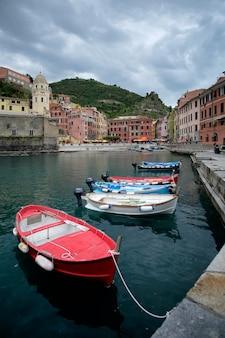 Dramatyczne zachmurzone niebo nad portem vernazza, z kilkoma łodziami na pierwszym planie. cinque terre, włochy.