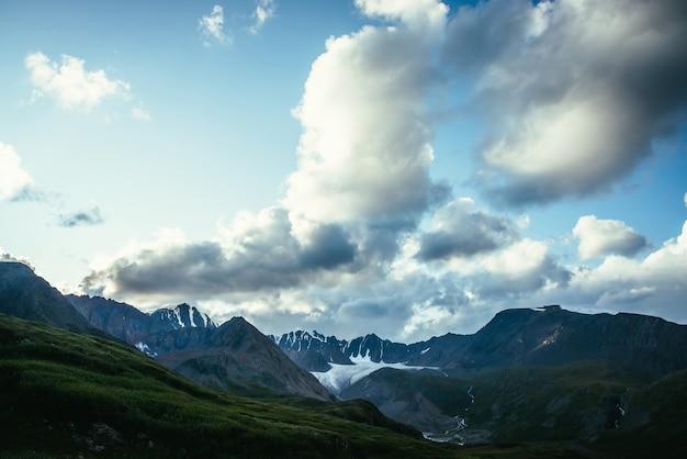 Dramatyczny Alpejski Krajobraz Z Grzbietem Górskim Pod Zachmurzonym Niebem. Duża Chmura W Błękitne Niebo Nad Sylwetkami Pasma Górskiego. Duża Chmura W Gradientowym Niebie Nad Sylwetkami Gór I Pięknym Lodowcem Premium Zdjęcia