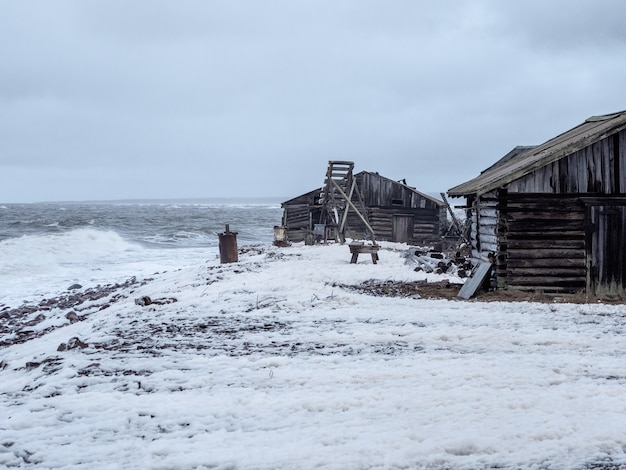 Dramatyczny krajobraz morski z szalejącym morzem białym i chatą rybacką na brzegu. zatoka kandalaksha. umba. rosja.