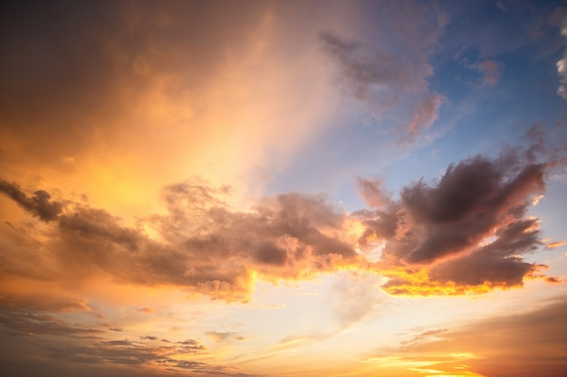 Dramatyczny krajobraz zmierzchu z bufiastymi chmurami oświetlonymi pomarańczowym zachodzącym słońcem i niebieskim niebem.