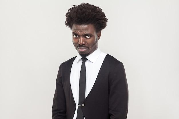 Dramatyczny płacz człowieka afro i patrząc na kamery. studio strzał, szare tło
