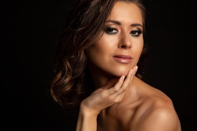 Dramatyczny portret atrakcyjna brunetka opalona model z doskonały makijaż i nagie ramiona pozowanie studio. miejsce na tekst