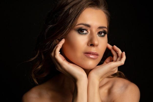Dramatyczny portret glamour opalonej brunetki z idealnym makijażem i nagimi ramionami pozujących w studio