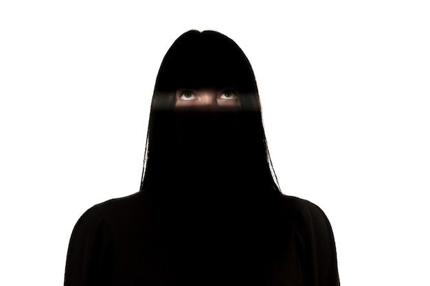 Dramatyczny portret młodej dziewczyny w ciemności na białym tle na ścianie białego studia