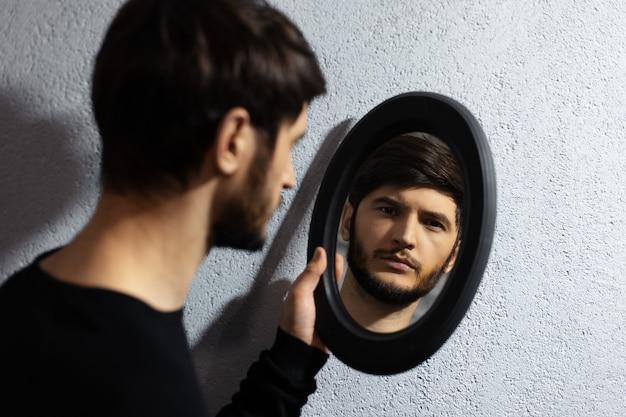 Dramatyczny portret młodzieńca patrząc w lustro.