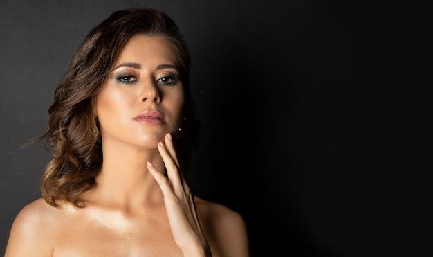 Dramatyczny portret oszałamiająca brunetka opalona modelka z doskonałym makijażem i nagie ramiona pozowanie w studio. miejsce na tekst