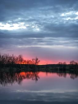 Dramatyczny różowy zachód słońca nad leśnym jeziorem z sylwetką nagich drzew na horyzoncie