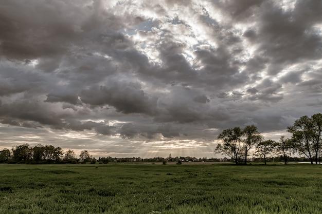 Dramatyczny widok na krajobraz z promieniami słonecznymi świecącymi przez ciemne pochmurne niebo