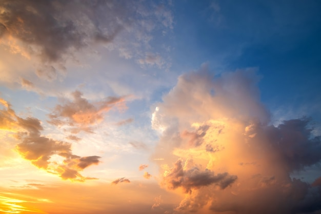 Dramatyczny zachmurzony zachód słońca krajobraz z podpuchniętymi chmurami oświetlonymi pomarańczowym zachodzącym słońcem i błękitnym niebem.