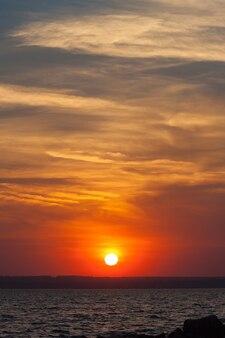 Dramatyczny zachód słońca nad morzem. zachodzące słońce na czerwonym niebie