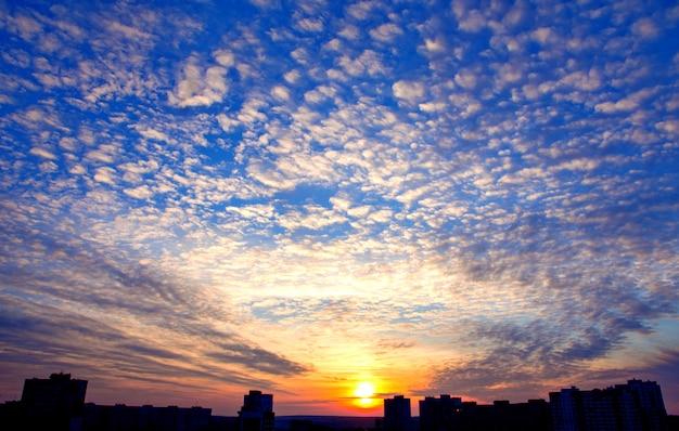Dramatyczny zmierzchu nieba tło z ognistymi chmurami