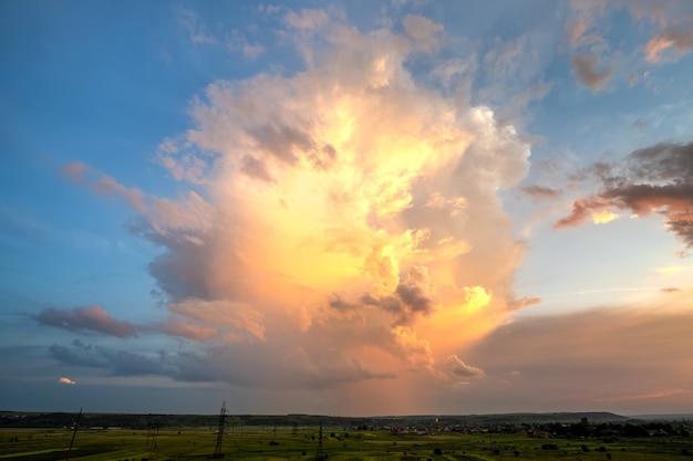 Dramatyczny żółty zachód słońca nad obszarem wiejskim z burzowymi podpuchniętymi chmurami