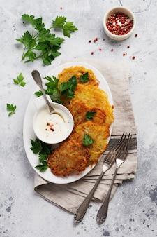 Draniki - placki ziemniaczane, wegetariańskie placki ziemniaczane, podawane ze świeżymi ziołami i sosem jogurtowo-czosnkowym, widok z góry