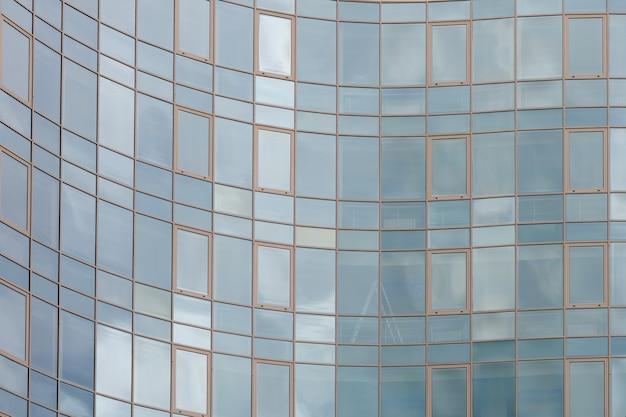 Drapacza chmur lustrzana szklana powierzchnia odbija chmurnego niebo, zakrętowa powierzchnia