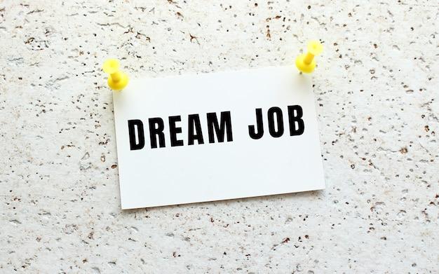 Dream job jest napisany na karcie przyczepionej do białej, teksturowanej ściany za pomocą przycisku. przypomnienie o biurze. pomysł na biznes.