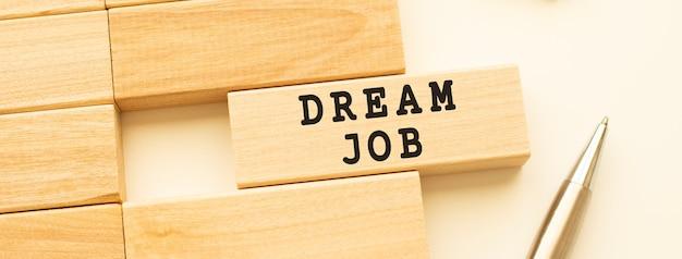 Dream job tekst na listwie leżącej na białym stole z metalowym długopisem.