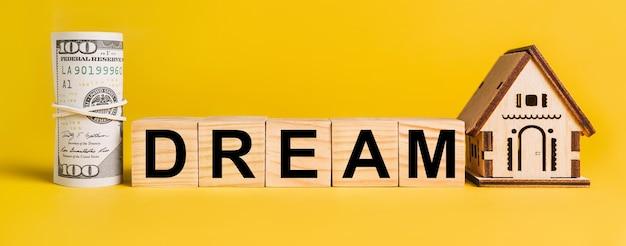Dream z miniaturowym modelem domu i pieniędzmi na żółtym tle. pojęcie biznesu, finansów, kredytu, podatków, nieruchomości, domu, mieszkania