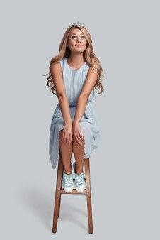 Dreaming about ... piękna młoda kobieta nosząca koronę i patrząca w górę siedząc na stołku na szarym tle