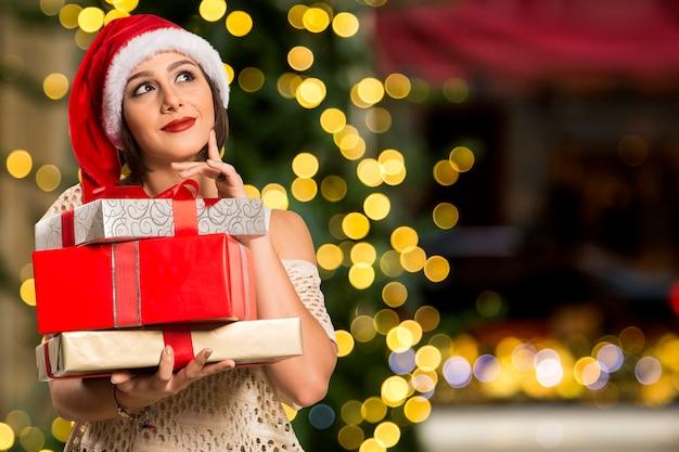 Dreaming myślenie szczęśliwa zamyślona piękna kobieta w czerwonym kapeluszu święty mikołaj / prezenty, boże narodzenie, koncepcja x-mas