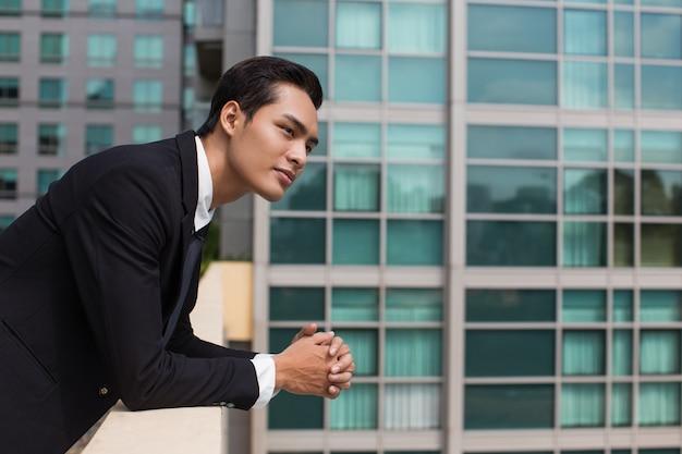Dreamy biznes człowiek leaning na balustrada na świeżym powietrzu