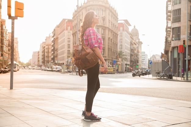 Dreamy młoda kobieta, stojąca na ulicy