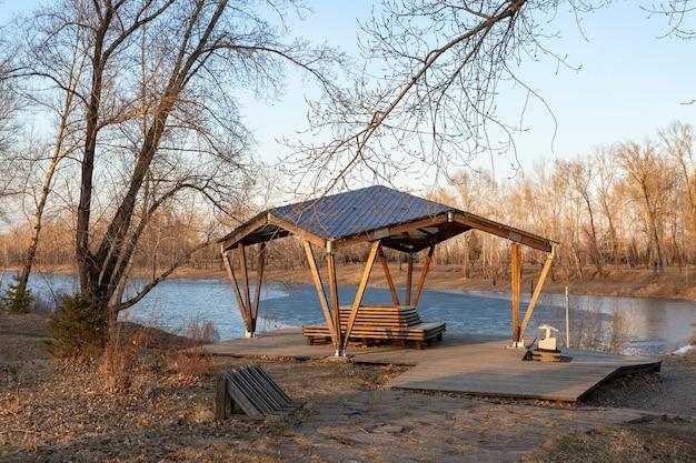 Drewniana altana w parku nad brzegiem zalewu