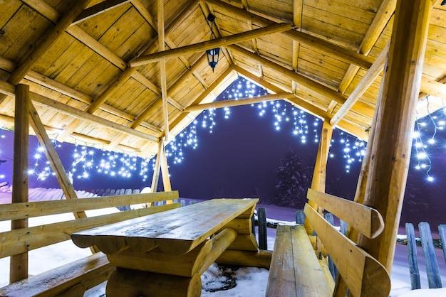 Drewniana altana z lampkami choinkowymi stoi wieczorem na stoku narciarskim w mglistej zimie na tle ośnieżonych jodeł