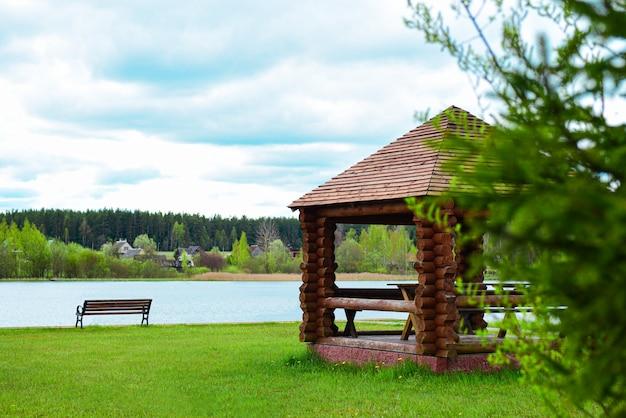 Drewniana altana z ławką na brzegu jeziora leśnego