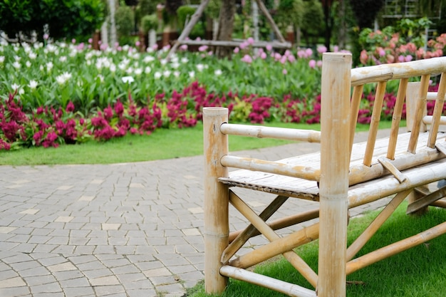 Drewniana bambusowa ławka w kwiatu ogródzie