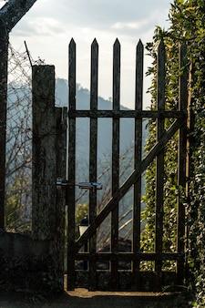 Drewniana brama w miejscu przypominającym piękny widok na góry i błękitne niebo za nim