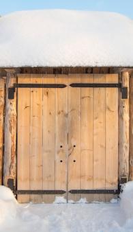 Drewniana brama w ogrodzeniu na pogodnym zima dniu