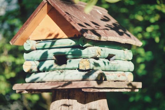 Drewniana budka dla ptaków w formie domu na niewyraźnym tle drzew