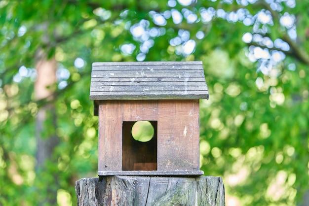 Drewniana budka dla ptaków w formie domu z rozmytym tłem drzew