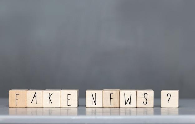Drewniana budka z napisem fake news na szarej ścianie, koncepcja mediów społecznościowych fake news