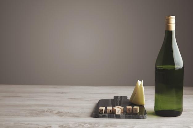 Drewniana cegła z literą w pobliżu pokrojonego koziego sera i pół pustej butelki z zielonego wina z winogron na białym tle na marmurowej kamiennej płycie na białym drewnianym stole i szarym neutralnym tle