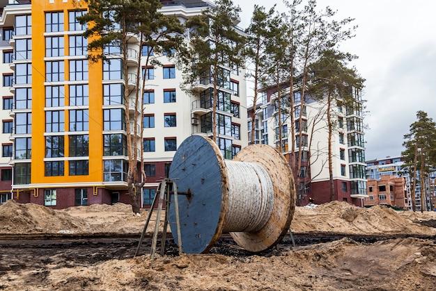 Drewniana cewka kabla elektrycznego na budowie na tle budynku mieszkalnego.