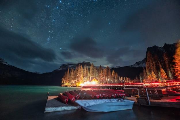 Drewniana chata i kajak zaparkowany z gwiazdami na jeziorze emerald w parku narodowym yoho w kanadzie